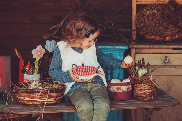 child girl playing with easter eggs and handmade decorations in cozy country house